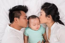 mom dad and baby in bed